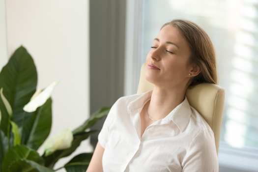 Calm attractive woman feeling relaxed leaning back on office cha